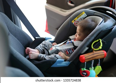 cute baby boy sleeping in car seat safety belt lock protection drive road trip travel