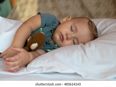 cute baby boy sleeping on the bed at home with toy