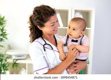 Cute baby boy smiling at his doctor while she holds him in her arms