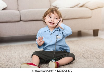 Cute baby boy talking with imaginary friend on cellphone, playing on floor at home, copy space