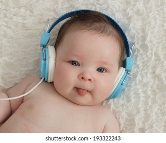 Cute baby boy wearing blue headphones and sticking tongue out