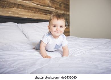A Cute Baby boy in white bedding.
