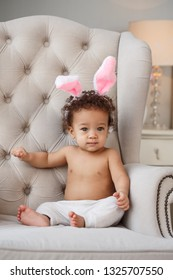 Cute baby with bunny ears on the chair in the room