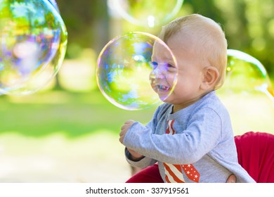 Cute baby catching soap bubbles in a summer day