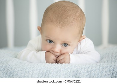 Cute baby caucasian boy lying on a soft blanket in a white crib.