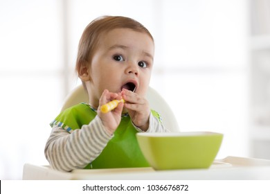 Cute baby child eats healthy food himself with spoon. Portrait of happy kid boy with bib in high chair.