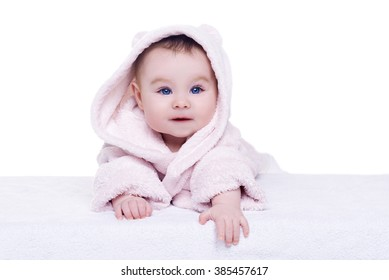 cute baby child in pink bathrobe hood lying down and try crawl, isolated. baby with blue eyes smiling and looking into the camera. happy family concept