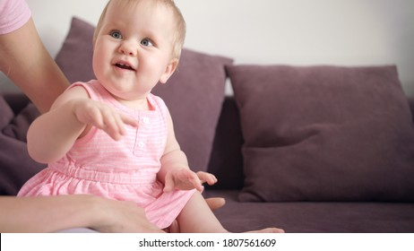 Cute baby child smiling in mother embrance. Close up of sitting kid playing with toy. Beautiful infant sitting on sofa and playing with parents. Sweet childhood. Adorable child smile to father