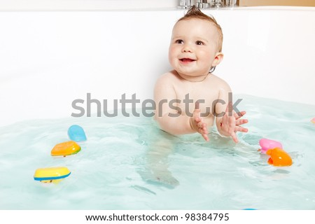 Cute baby clapping hands and smiling while taking a bath