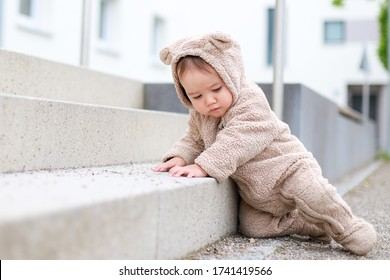 Cute baby climbs up the stairs development.infant boy wearing warm clothes teddy bear costume playing on the stairs outdoor background.mixed race Asian-German child play and learning.