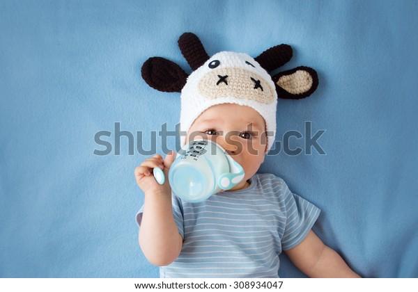 bambino carino in un cappello di mucca bere latte