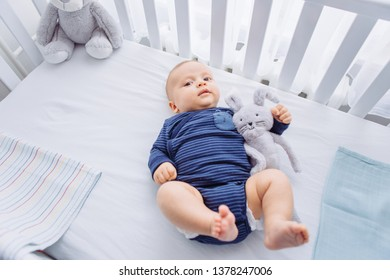 Cute baby in crib with toy friends