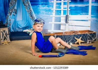 Cute baby in a diving suit and flippers on a summer marine studio background. Active sport, sports fashion