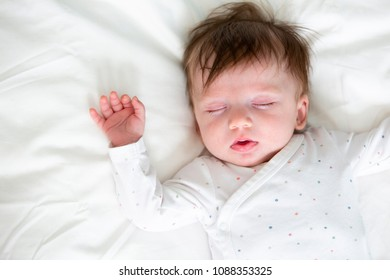 cute baby with dotted body is lying in bed