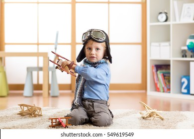 Cute baby dreaming of being pilot. Little child boy playing with toy airplanes.