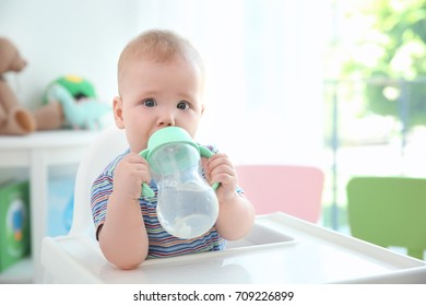 Cute baby drinking water from plastic bottle indoors