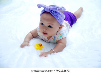 a cute baby with a duck toy on a white background