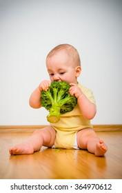 Cute baby eating broccoli sitting on floor indoors