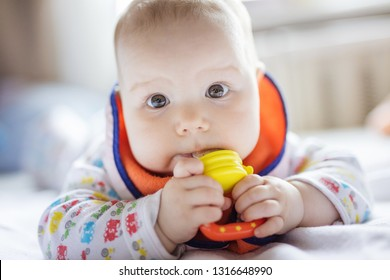 Cute baby eating fruit in nibbler on bed at home
