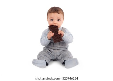 Cute baby eating a plate of chocolate. Studio isolated on white background.