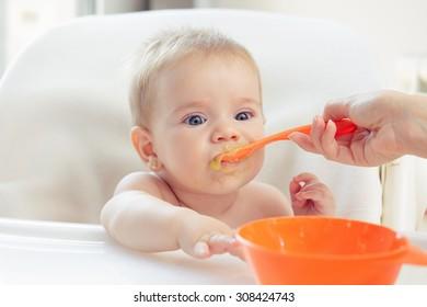 Cute baby eating puree