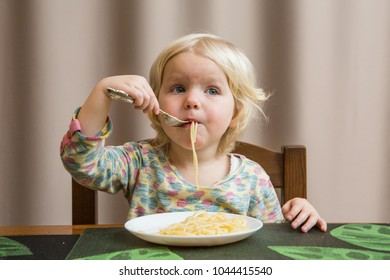 cute baby eating spaghetti sitting at table