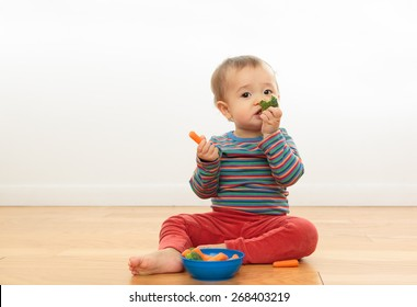 Cute baby eating vegetables. Infant sitting up holding carrots and broccoli. Baby eating healthy foods. Baby's first foods. One year old in striped shirt eating nutritious snacks. Child wearing orange