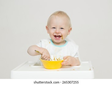 Cute baby eating in white high chair against white background with a yellow bowl.