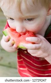 cute baby eats a juicy slice of watermelon