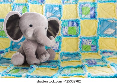 Cute Baby Elephant Stuffed Animal on a Colorful Quilt