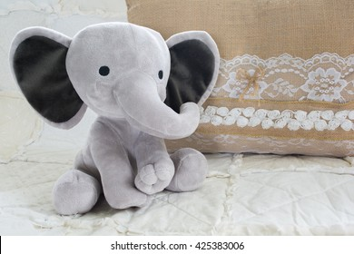 Cute Baby Elephant Stuffed Animal on White Quilt with Burlap