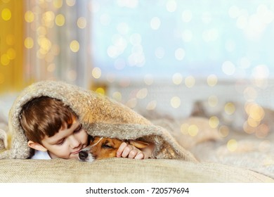 Cute baby embracing and sleeping under wool blanket in early morning christmas day.