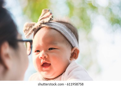 cute baby enjoy playing with aunt in park at sunset