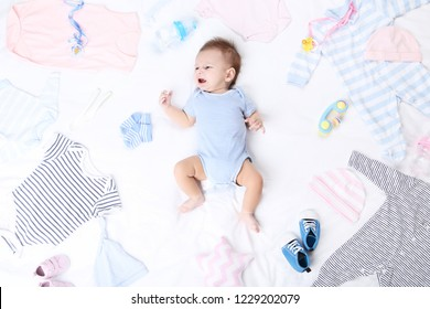 Cute baby with fashion clothes lying on white bed