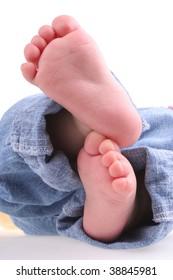 Cute baby feet in denim jeans.