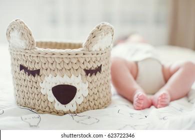 cute baby feet near crochet teddy bear basket