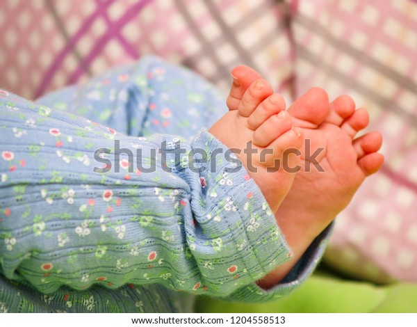 Cute baby feet in soft light blue body pants with tiny flowers, lying on the bed