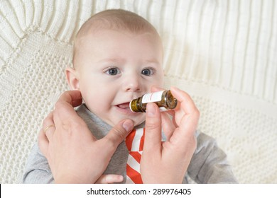 Cute baby gets medicine from a little bottle