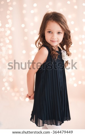 Cute Baby Girl 5 6 Year Old Wearing Stylish Dress Over Lights In Room Looking At Camera Birthday Party Celebration