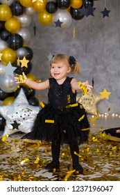 Cute baby girl in airy black dress posing in party studio with golden stars and air baloons. Pillow stars SUPER STAR designed by photographer