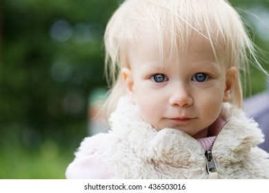 Cute baby girl with blonde hair outdoors. Little girl 1-2 year old, close-up