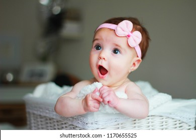 Cute baby girl, with a bow on her hair, with amazement face