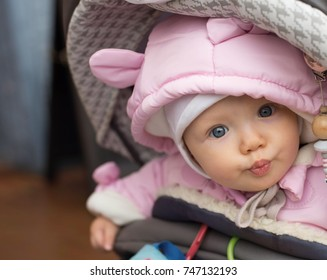 Cute baby girl in baby buggy making kiss.