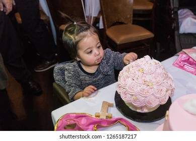 Cute baby girl celebrating first birthday party taste pink frosting on cake. New sweet foods for baby to dip fingers into and put icing in mouth.