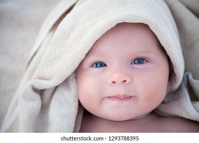 cute baby girl covered with a bath beige towel