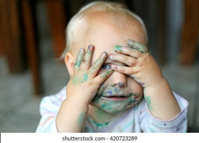 Cute Baby Girl Covering her messy, painted face with her dirty hands