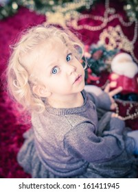 Cute baby girl with curly blond hair and big blue eyes playing with christmas decoration. Selective focus