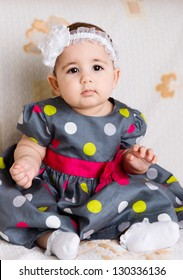 Cute baby girl in dotted dress sitting on sofa