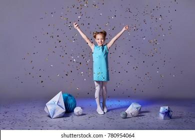 Cute baby girl dresses pretty model enjoying holiday and throwing confetti.fashion models of children .