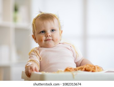 Cute baby girl eating her lunch and making a mess